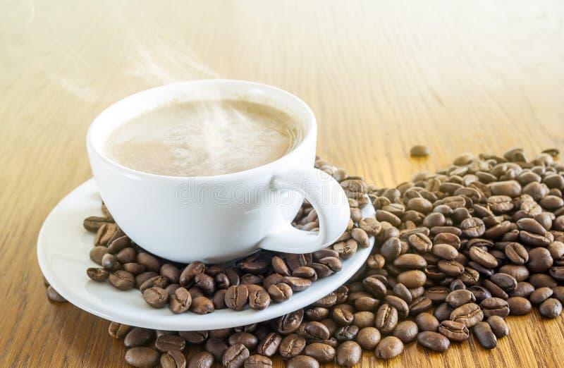 咖啡在一个白色杯子和咖啡豆的在木桌ba 免版税库存图片