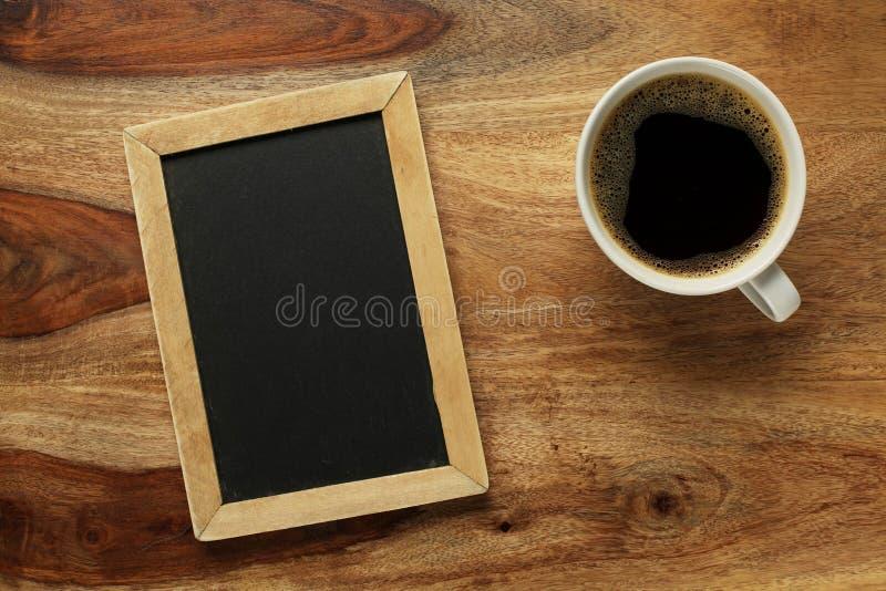 咖啡在书桌上的有黑板的 免版税图库摄影
