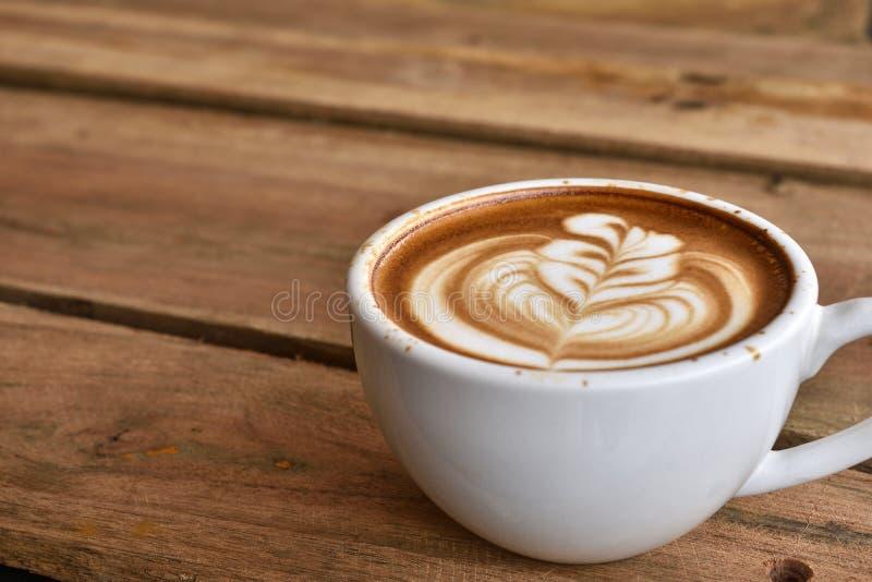 咖啡在加奶咖啡杯子的拿铁艺术 库存照片