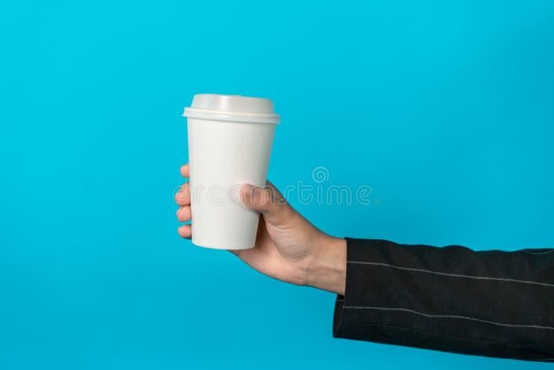 咖啡在女性手上有在框架的中心的浅兰的背景 在一个白皮书杯子的饮料 免版税库存照片