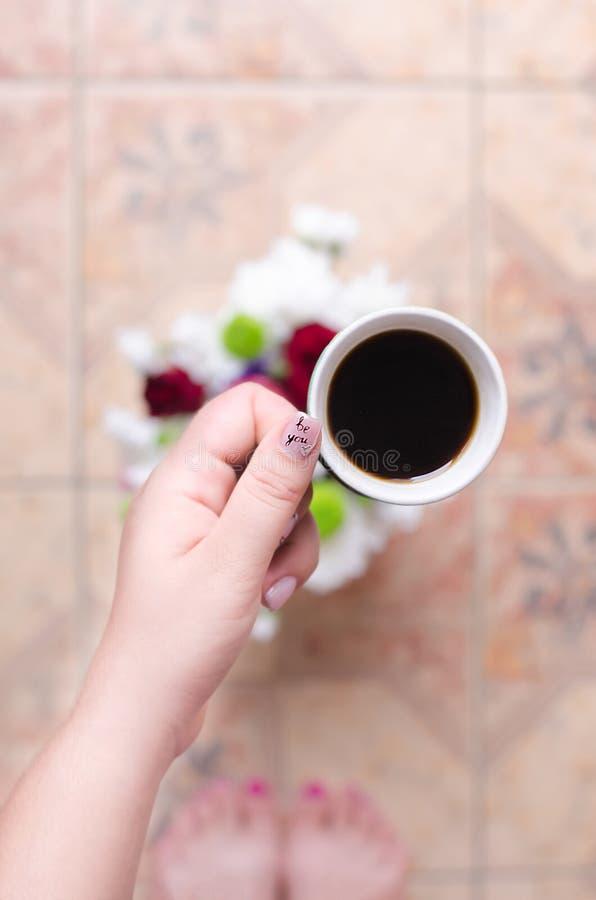 咖啡在手中在花背景  免版税库存照片