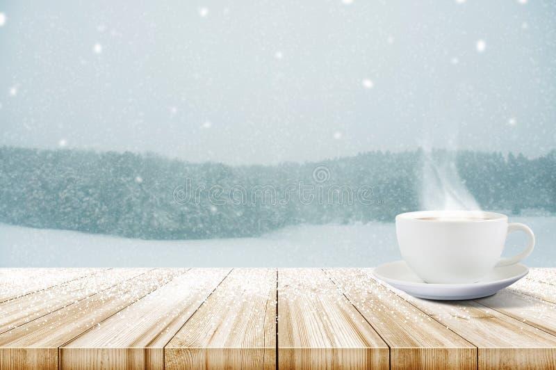 咖啡在木桌上的与冬天降雪报道了前面 免版税库存照片