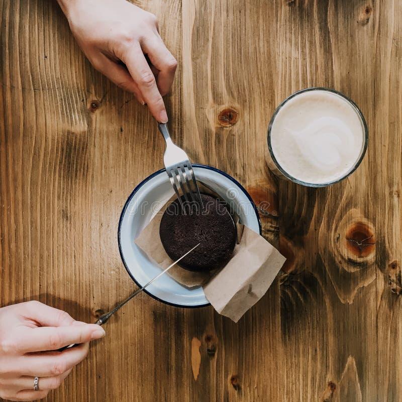 咖啡在木桌上的和巧克力蛋糕 有切开蛋糕的叉子和刀子的手 Squred照片葡萄酒盘 库存照片