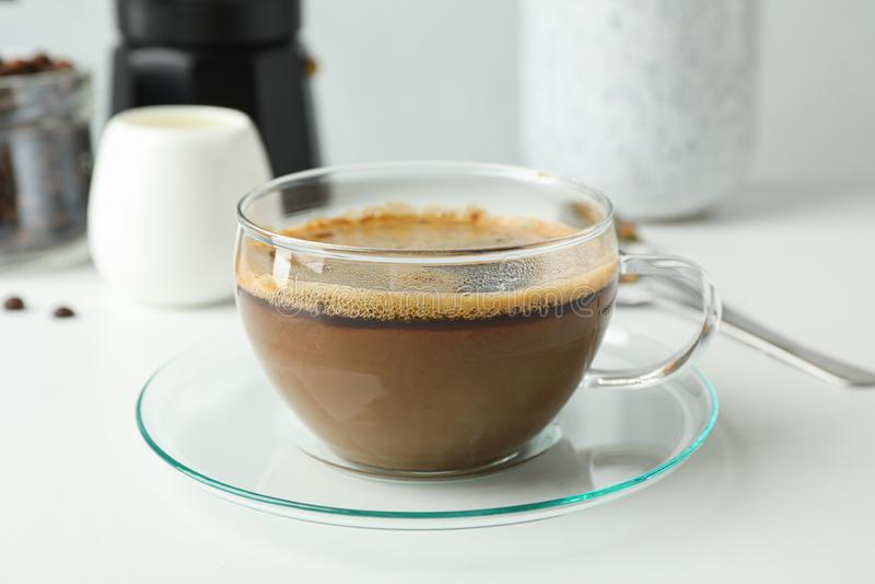 咖啡在白色桌反对轻的背景,空间文本的和特写镜头上的时间辅助部件 免版税库存图片