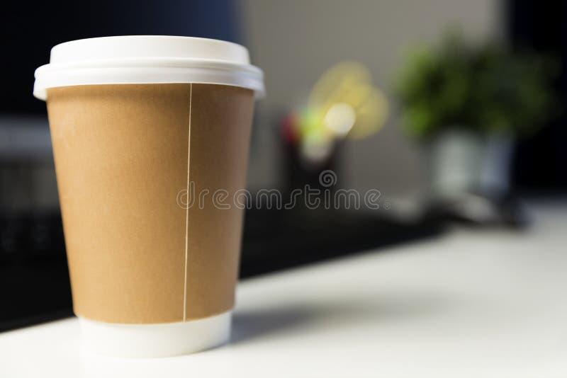 咖啡在计算机旁边的办公室 运作的晚概念 库存照片
