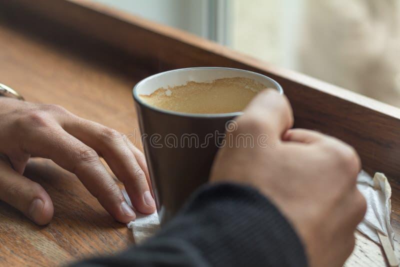 咖啡在说谎在咖啡馆的一张桌上的一个人的手上 库存图片
