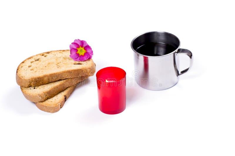 咖啡在钢杯子、三个油煎方型小面包片和一个红色蜡烛 库存照片