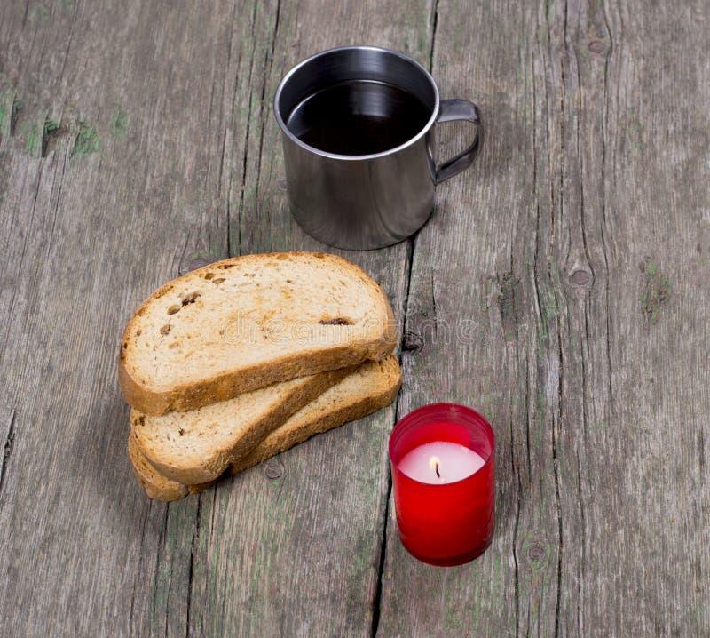 咖啡在钢杯子、三个油煎方型小面包片和灼烧的蜡烛 免版税库存照片