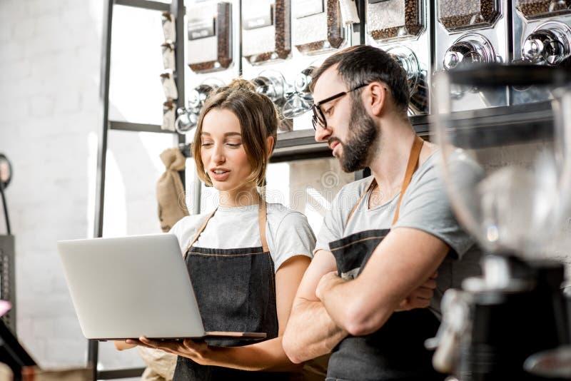 咖啡店主与膝上型计算机一起使用户内 免版税库存照片