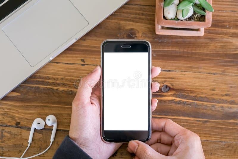 咖啡店木桌上手持笔记本电脑和耳袋的男式手持智能手机 带空白屏幕的手机,可以添加 免版税库存图片
