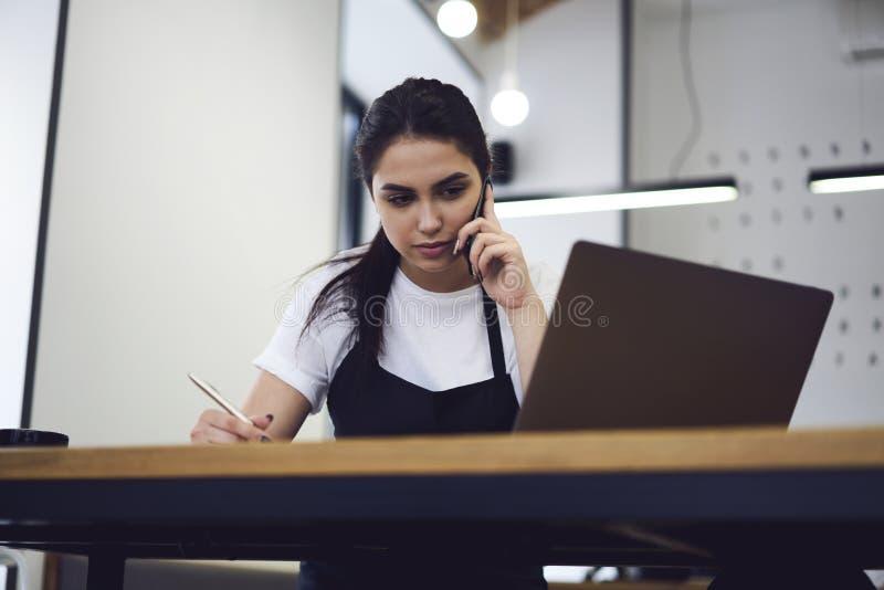 咖啡店的年轻女性企业家与纸张文件一起使用 免版税图库摄影