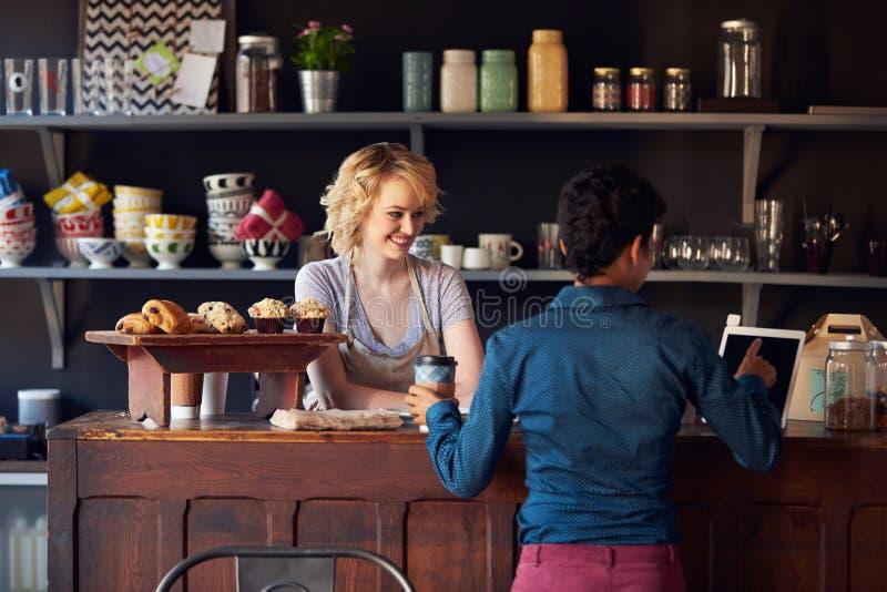 咖啡店的顾客预定使用数字式片剂 库存照片