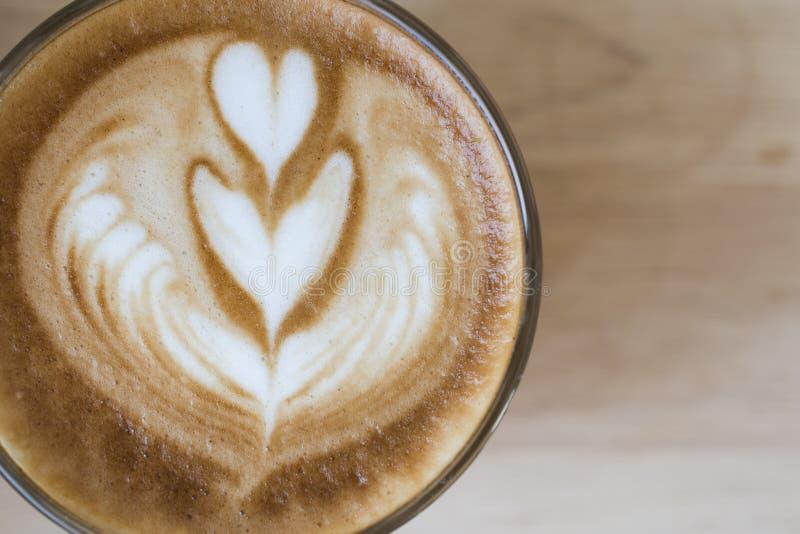 咖啡拿铁在咖啡馆葡萄酒颜色口气的艺术浓咖啡 与美丽的泡沫咖啡杯的热奶咖啡 拿铁艺术心形上面 免版税库存照片