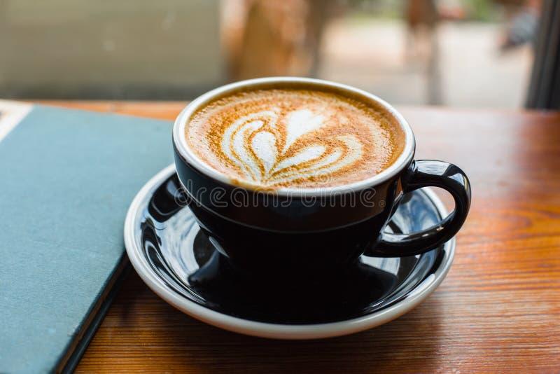 咖啡拿铁withj在窗口的一本书 免版税库存照片