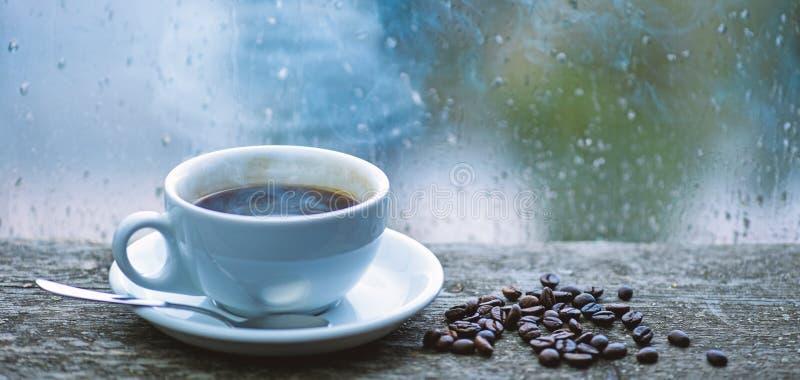 ( 咖啡早晨仪式 新鲜的酿造的咖啡白色杯子和豆在窗台 湿玻璃 免版税库存照片