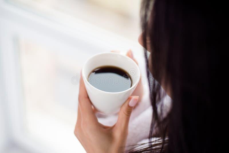 咖啡时间!关闭喝热的咖啡的妇女播种的照片 库存照片