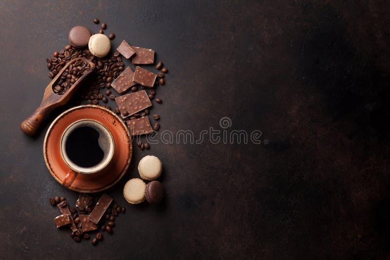 咖啡杯、巧克力和蛋白杏仁饼干在老厨房用桌上 库存图片