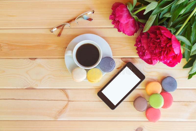 咖啡杯、巧妙的电话、玻璃和红色牡丹开花 免版税图库摄影