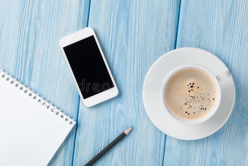 咖啡杯、智能手机和空白的笔记薄在木桌backgro 免版税库存照片