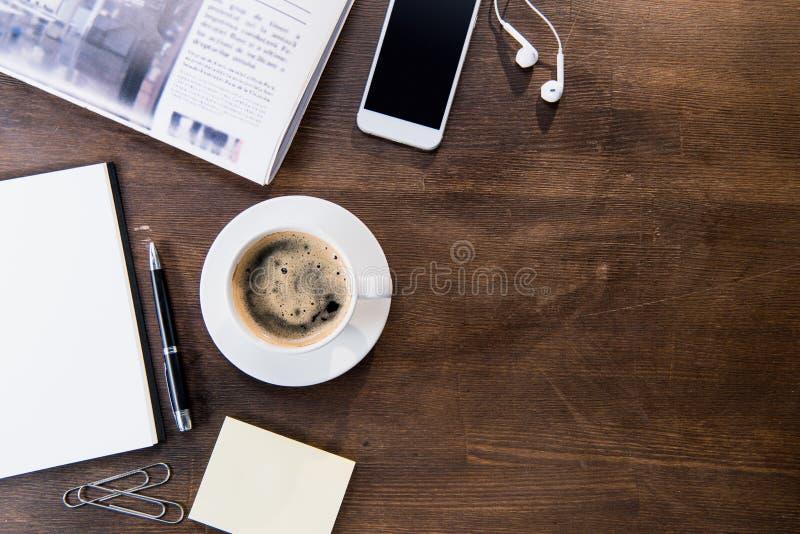 咖啡杯、智能手机有黑屏和耳机的,笔记本有笔的和报纸顶视图  免版税库存照片