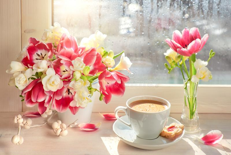 咖啡杯、桃红色郁金香和白色小苍兰-在窗台板, 库存照片