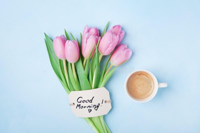 咖啡杯、桃红色郁金香花和笔记早晨好在蓝色台式视图 美丽的早餐在母亲或妇女天 免版税库存图片