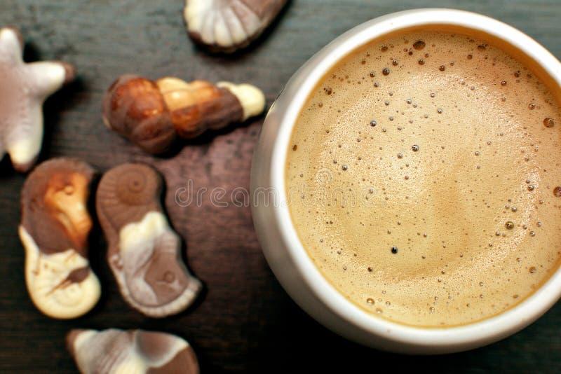 咖啡杯、热奶咖啡和食家比利时巧克力在一张木桌上 库存照片