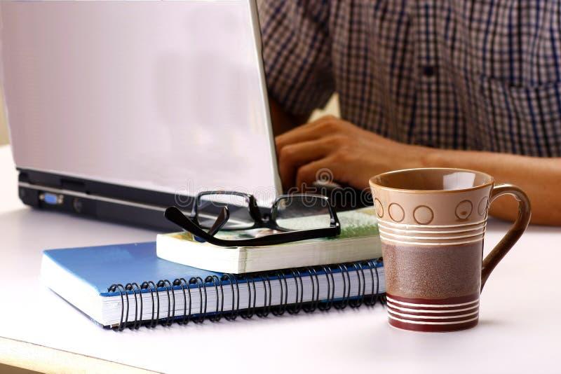 咖啡杯、研究一台便携式计算机的堆书和人在背景中 库存图片