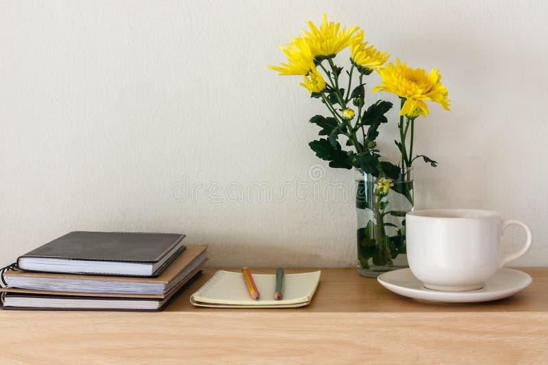 咖啡杯、笔记本、铅笔和花 免版税库存照片