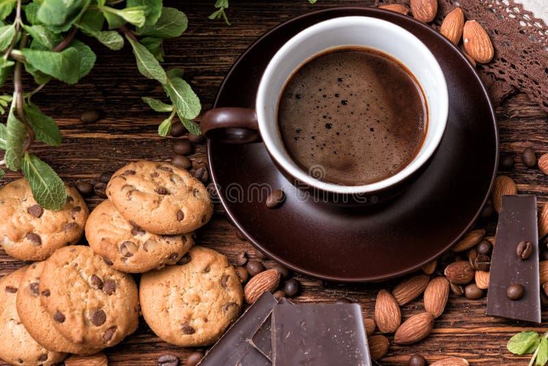 咖啡杯、豆、杏仁、巧克力和曲奇饼在老厨房用桌上 库存图片