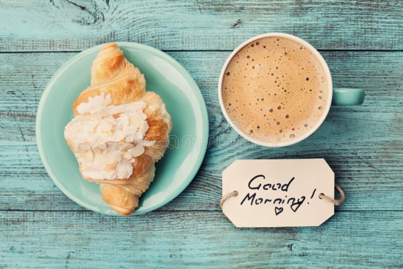 咖啡杯与在绿松石土气桌上的新月形面包和笔记早晨好从上面,舒适和鲜美早餐 图库摄影