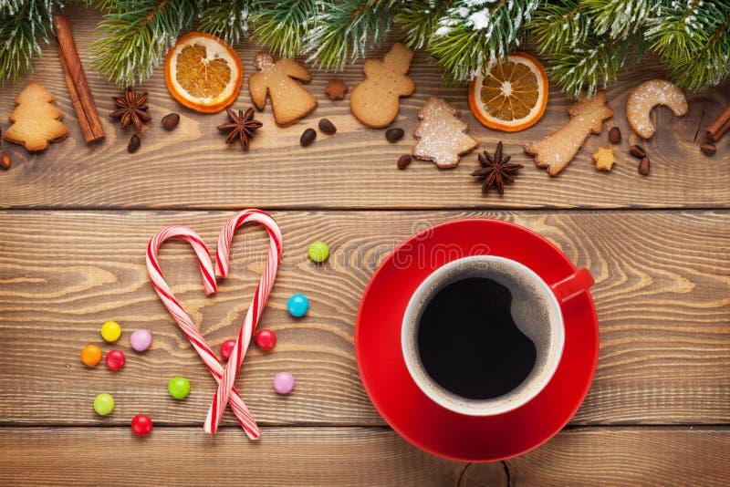 咖啡杯和圣诞节食物装饰在木背景 免版税库存照片
