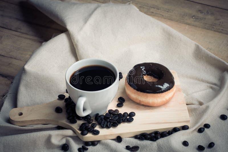 咖啡杯和多福饼与糖粉结冰在木板和 免版税库存照片