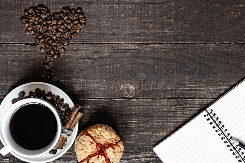 咖啡杯和心形的豆用桂香、曲奇饼和空白的笔记本 库存照片