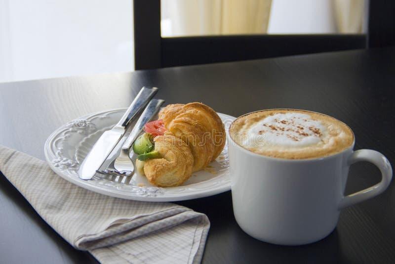 咖啡杯和新鲜的被烘烤的新月形面包在黑背景 图库摄影