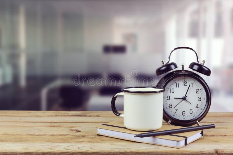 咖啡杯和时钟在木桌上在办公室内部 库存照片