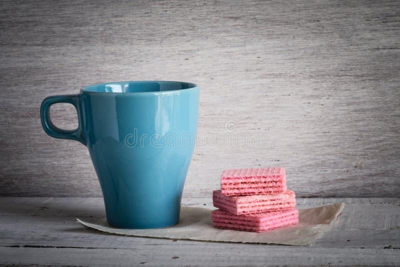 咖啡杯和桃红色奶蛋烘饼 免版税图库摄影