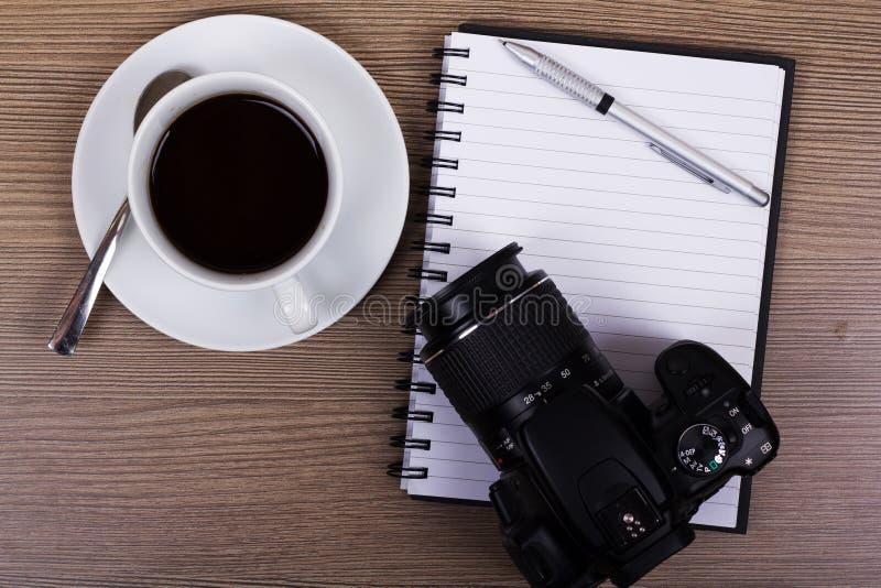 咖啡杯和照相机木表面上 免版税图库摄影