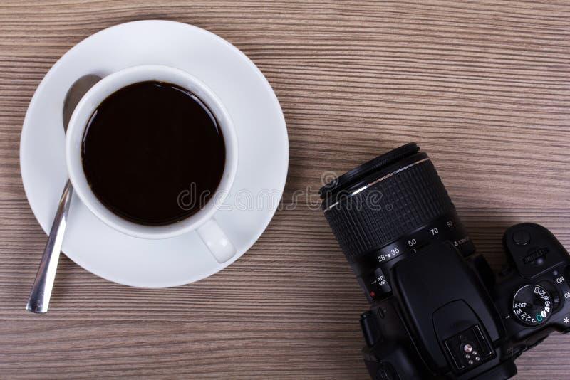 咖啡杯和照相机木表面上 库存照片