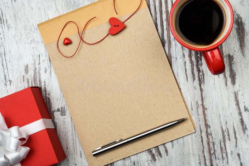 咖啡杯和空的笔记薄 库存照片