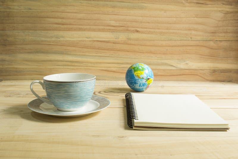 咖啡杯和笔记本在木桌上 库存图片