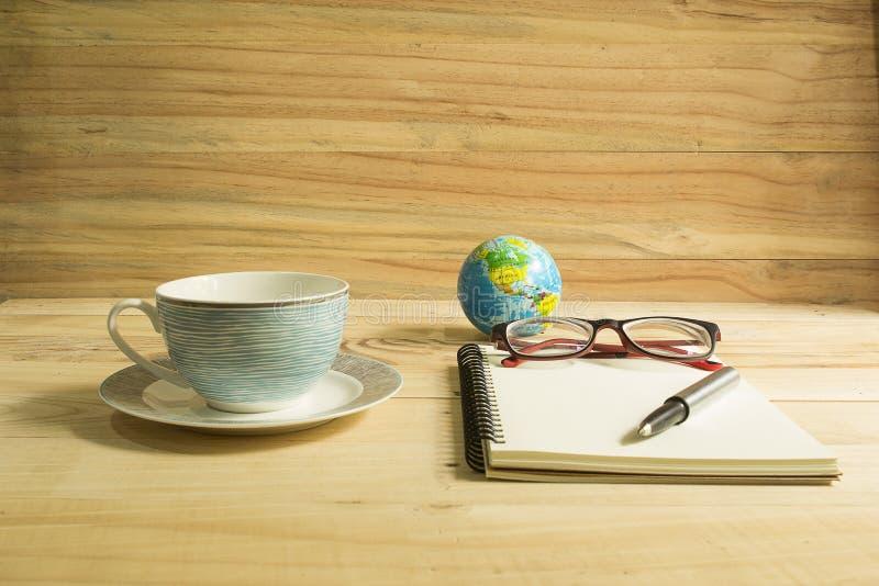 咖啡杯和笔记本在木桌上 库存照片