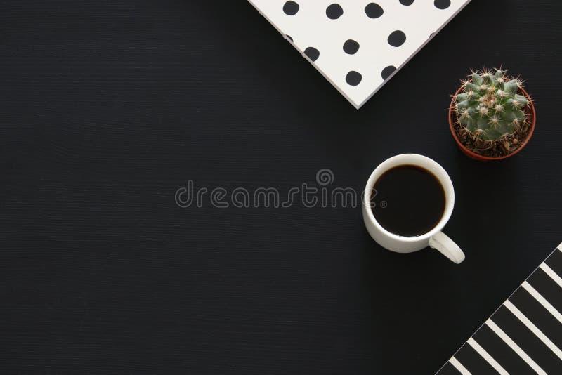 咖啡杯和笔记本的图象在黑背景 顶视图 免版税库存照片