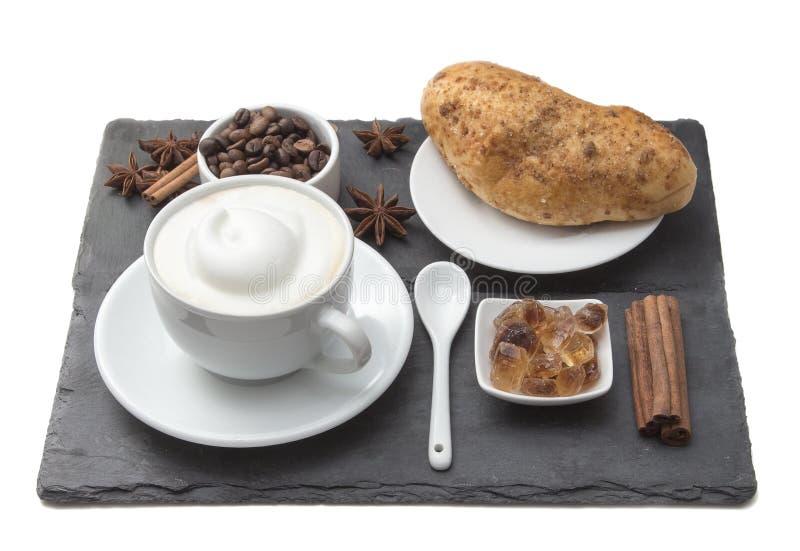 咖啡杯和蛋糕在桌上 与牛奶奶油的拿铁和热奶咖啡艺术 热的咖啡和小圆面包用肉桂条,咖啡 免版税库存照片