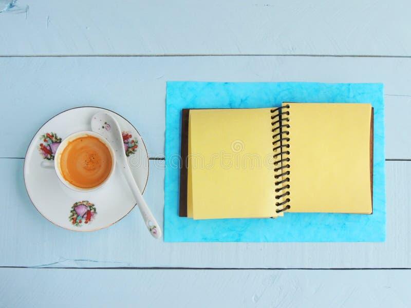 咖啡杯和螺纹笔记本在被绘的木背景 库存照片