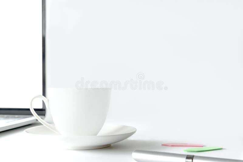 咖啡杯和计算机桌面在白色办公桌桌上与 库存照片