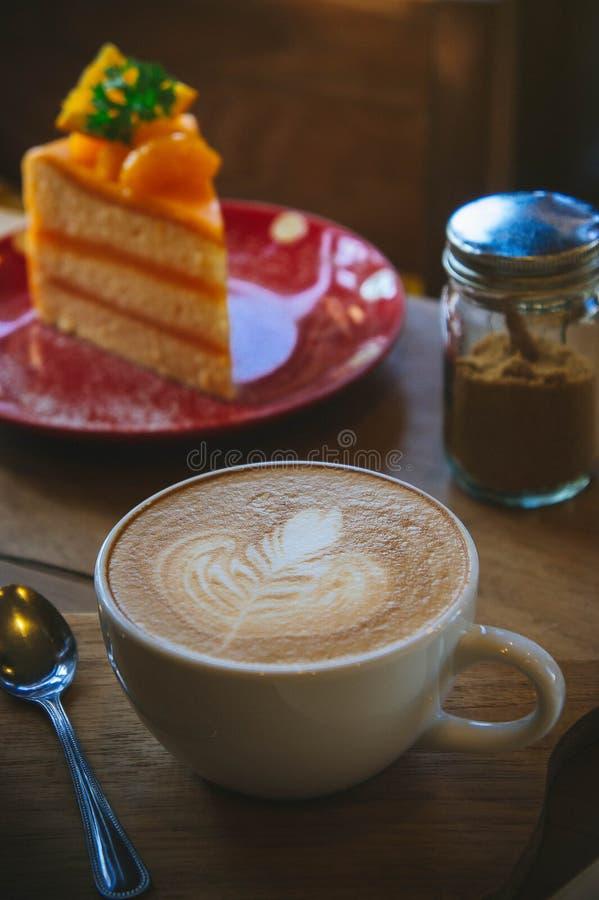 咖啡杯和鲜美蛋糕在木桌和白纸等待的想法,咖啡时间工作 库存照片