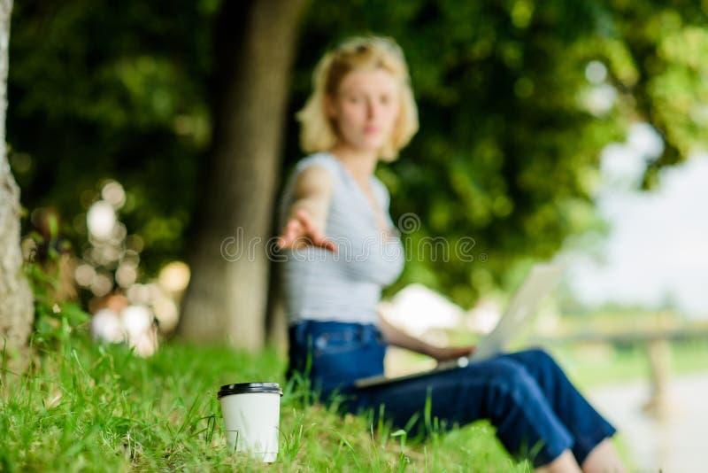 咖啡杯拿走接近射击 在绿草女工的咖啡杯有膝上型计算机defocused背景 ?? 免版税库存图片