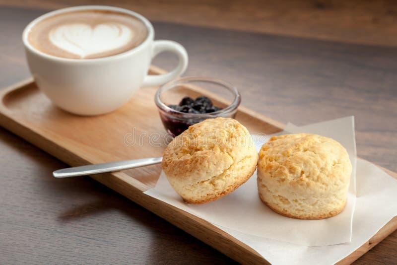 咖啡杯拿铁艺术服务与烤饼和自创blueberr 免版税库存图片
