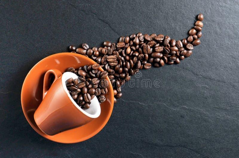 咖啡杯浓咖啡溢出的豆 免版税库存图片